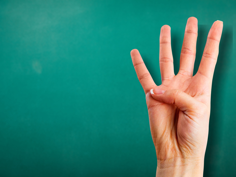 緑の背景の前で4を作る女性の手