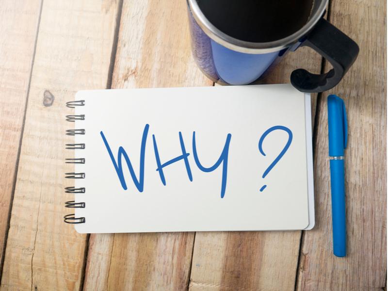 「WHY?」の文字が書かれた紙とマグカップ