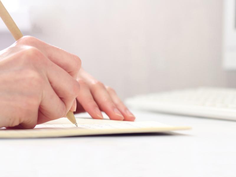 ペンを使ってノートに文字を書く手