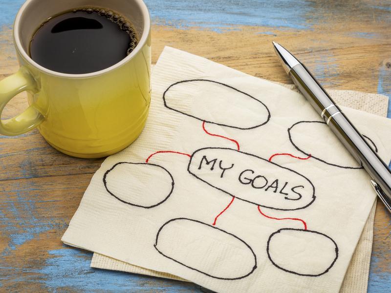 「MY GOALS」と書かれたナプキンとコーヒーが入った黄色のマグカップ