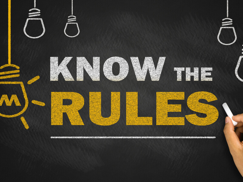 黒板に書かれた「KNOW THE RULES」の文字とチョークを持った手