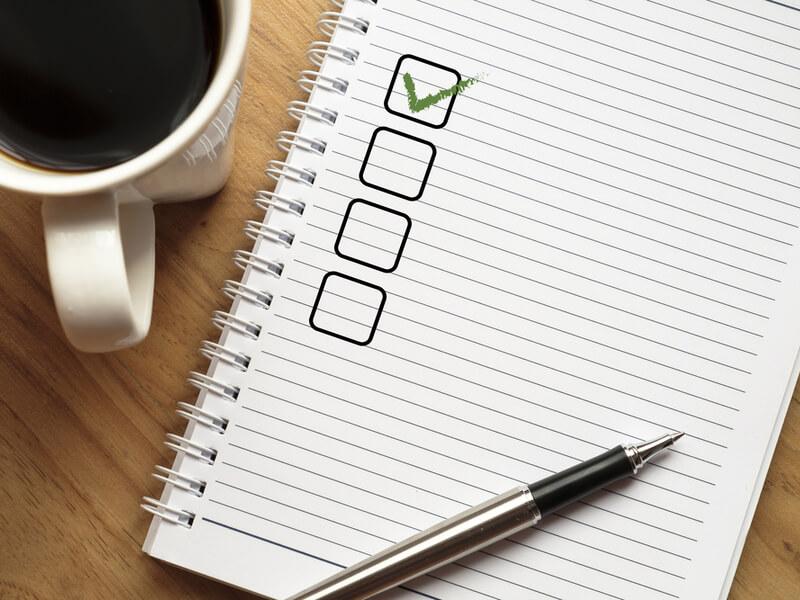 チェックリストが書かれたノートとコーヒーとペン