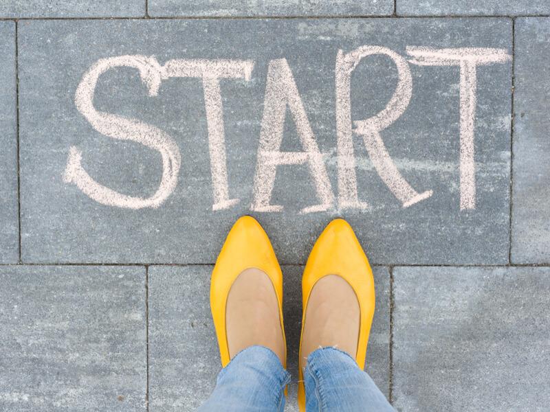 「START」と書かれた床とピンクの靴を履いた女性の足